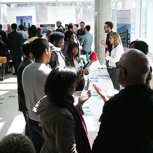 A crowd of students talking to tables at an Architecture event.